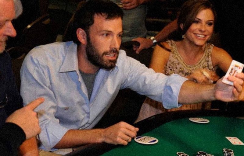 Ben Affleck holds a playing card