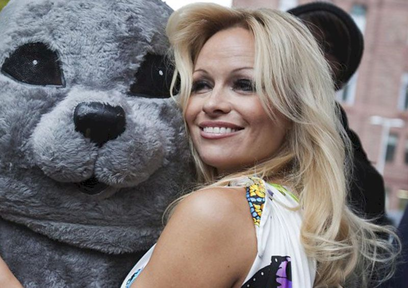 Pamela Anderson is standing with an animator