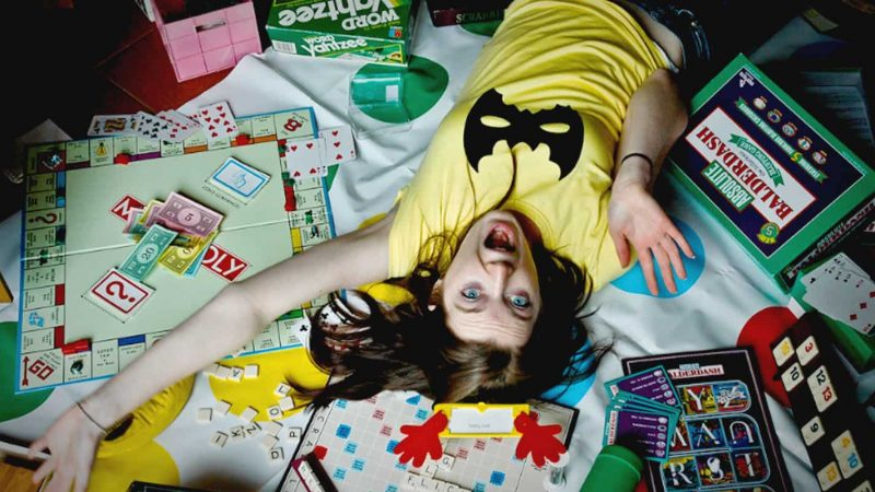 A girl lies on a monopoly game board